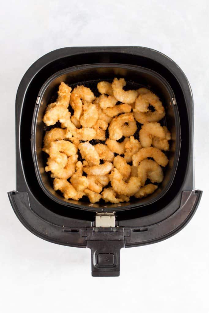 frozen breaded popcorn shrimp inside an air fryer basket.