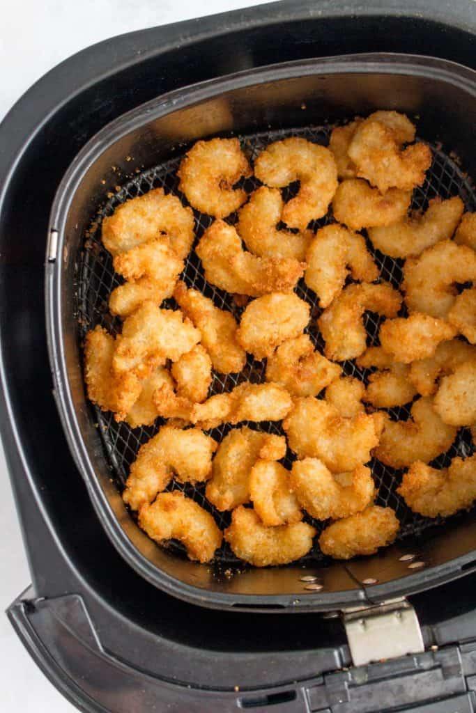 Breaded popcorn shrimp in an air fryer basket.