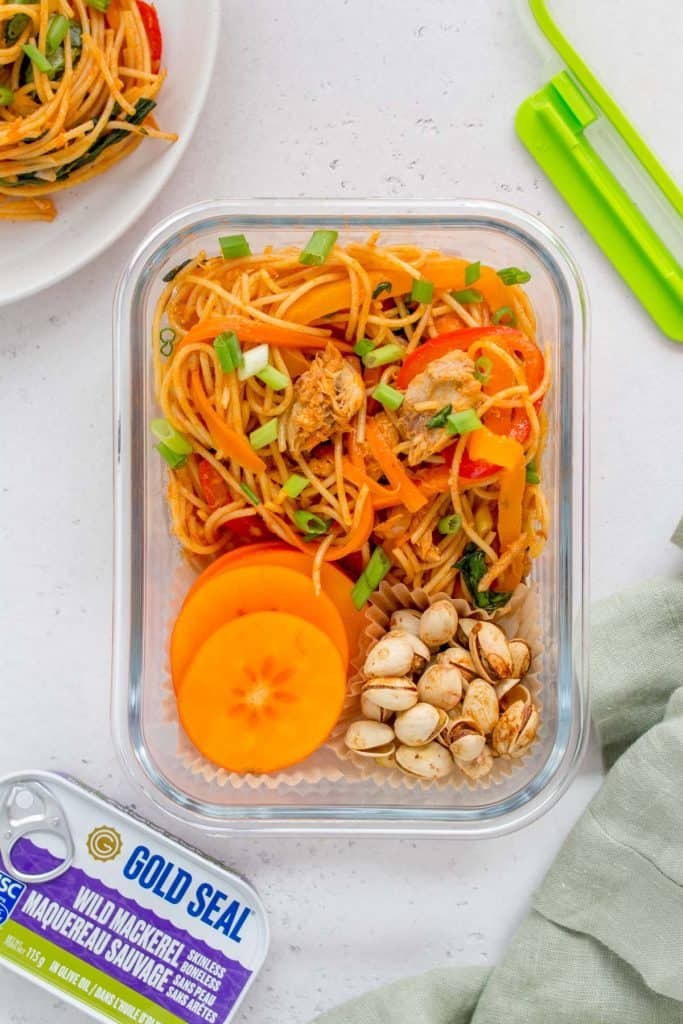 A meal prep container with a gochujang noodles with pistachio and sliced persimmons.