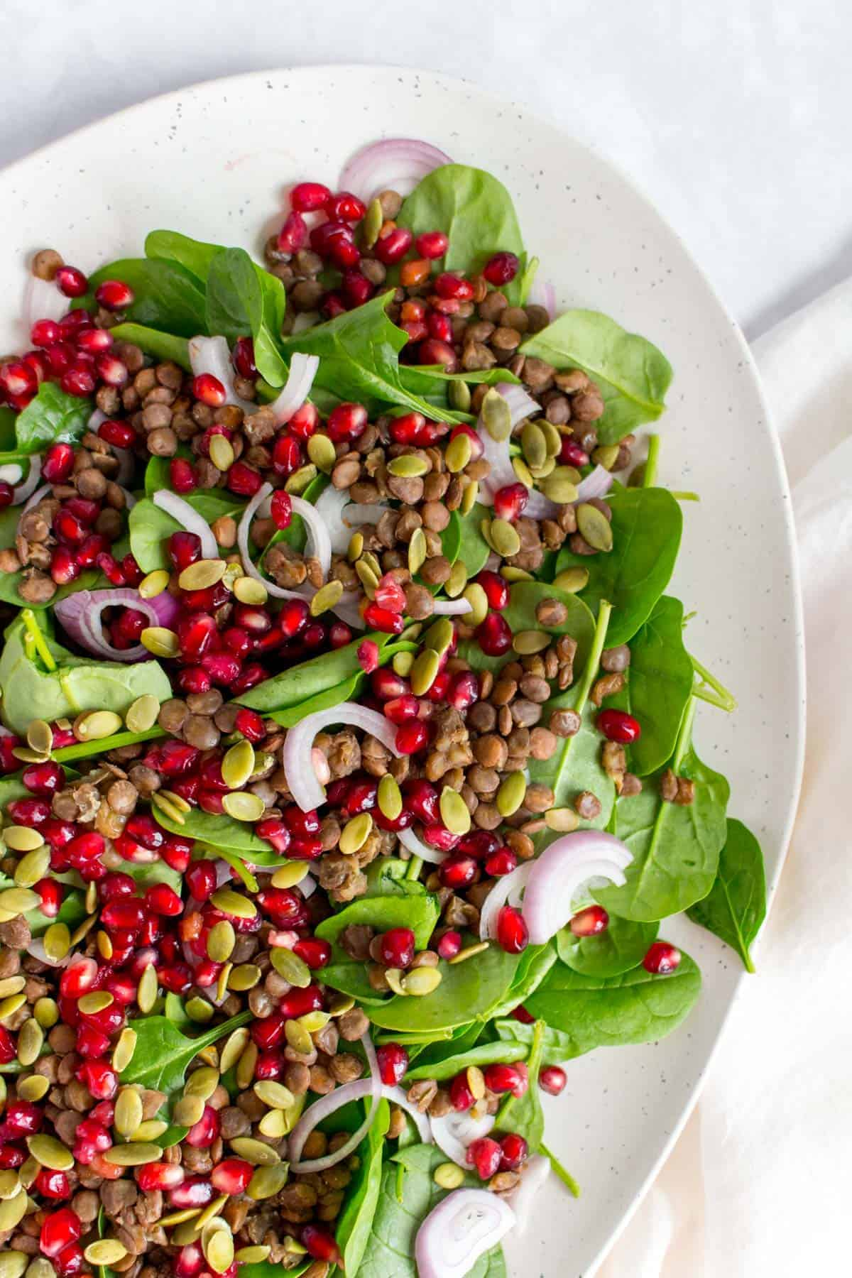 Close up of a white platter with spinach, pomegranate seeds, shallots, pumpkin seeds, and lentils.