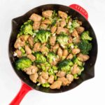 A red skillet with chicken and broccoli and edamame.