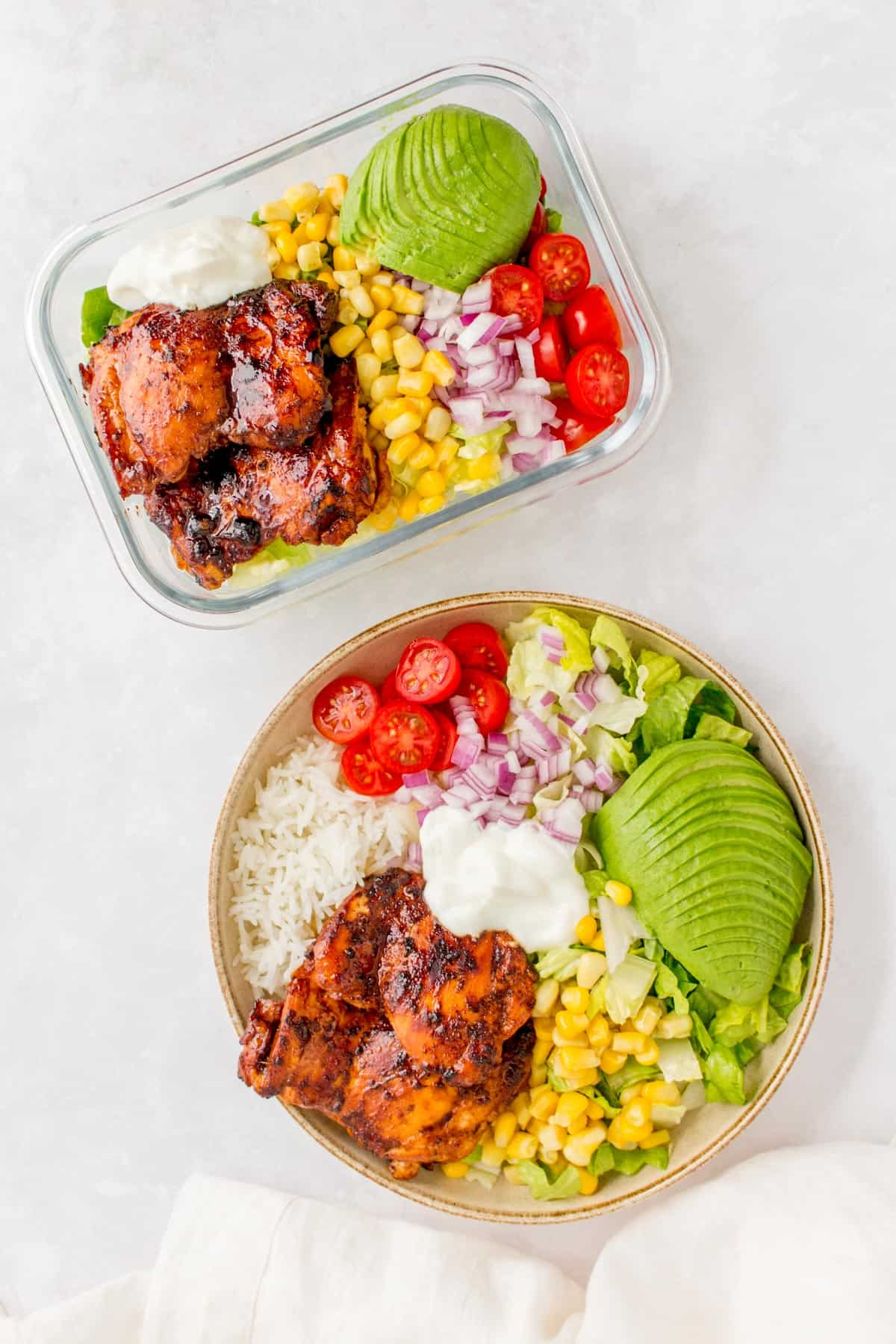 Overhead photo of a honey chipotle chicken salad in a meal prep container beside a burrito bowl.