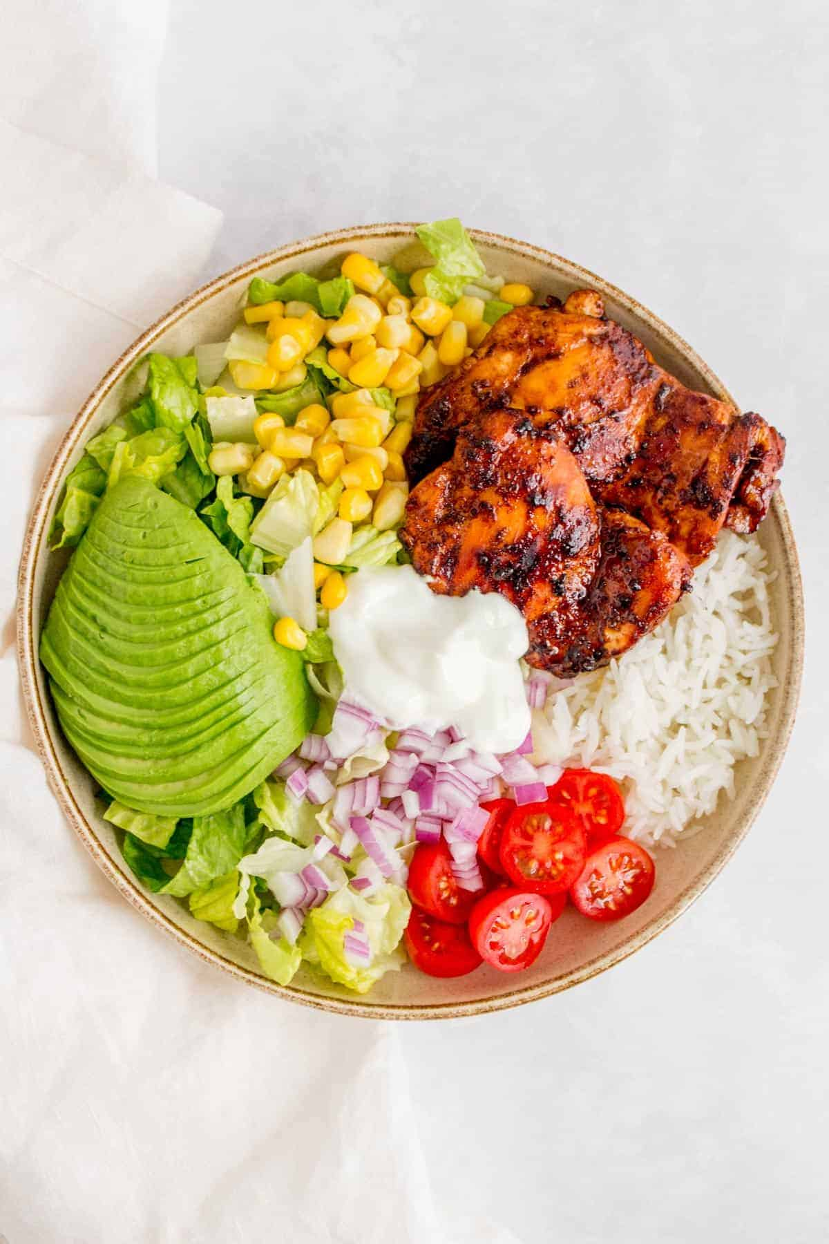 Honey chipotle chicken bowl with rice, corn, lettuce, tomatoes, onions, avocado, and sour cream.