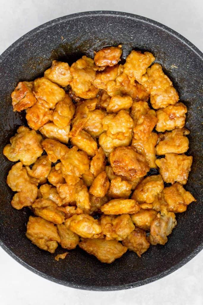 Crispy sesame chicken coated in sauce in a skillet.