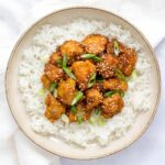 Sesame chicken over a bed of rice on a plate.