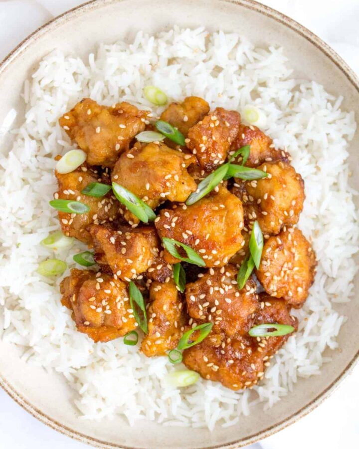 Close up of a plate of rice and crispy sesame chicken.