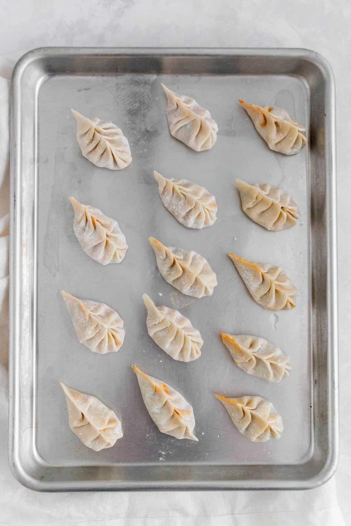 Frozen dumplings on a tray.