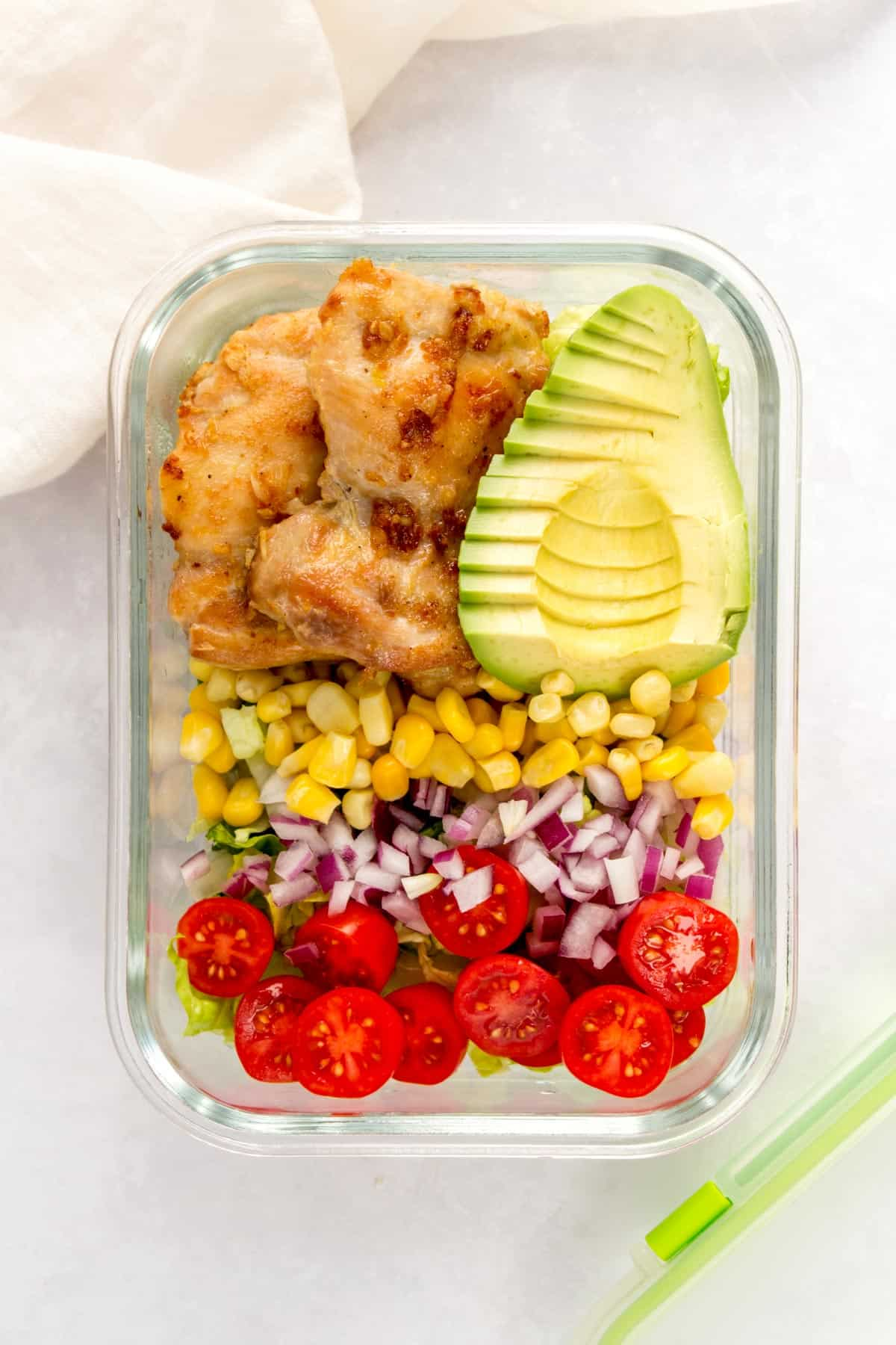 Meal prep container with lettuce, tomatoes, red onions, corn, chicken thighs, and a sliced avocado.