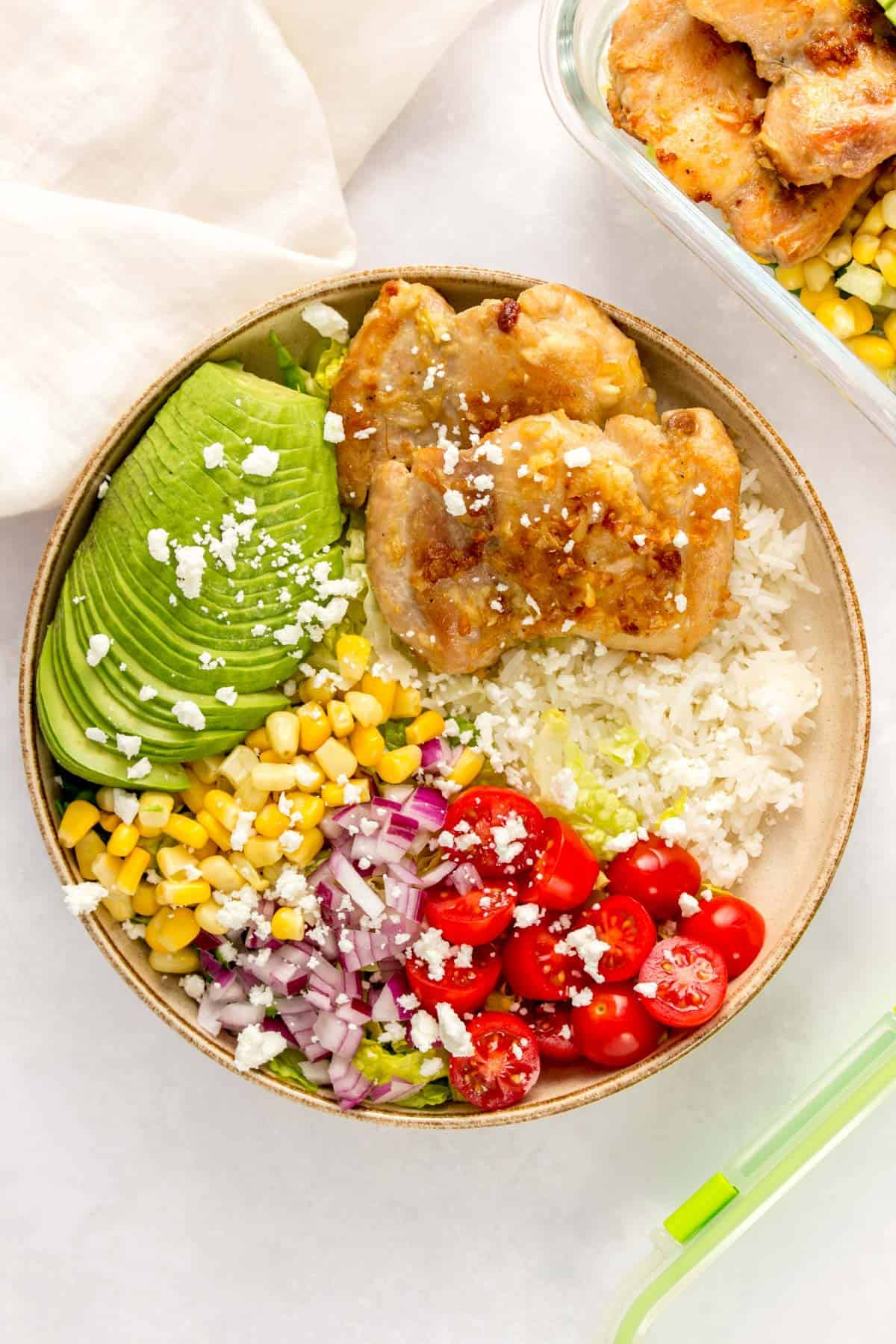 A plate with rice, lettuce, tomatoes, red onion, corn, avocado, and garlic butter chicken thighs.