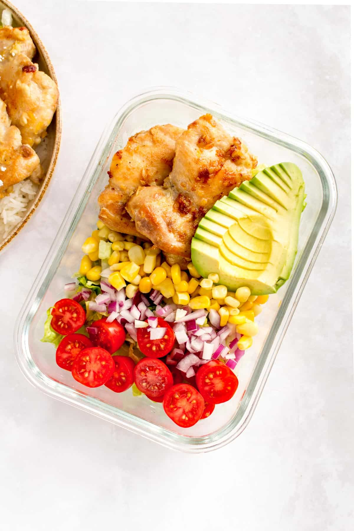 Glass meal prep container with lettuce, tomatoes, red onions, corn, chicken thighs, and a sliced avocado.
