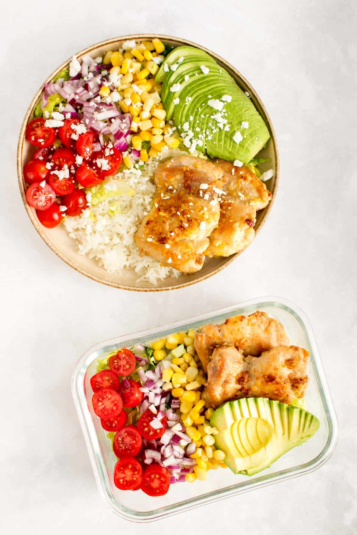 A plate with a chicken rice bowl and a meal prep container of a garlic butter chicken thigh salad bowl.