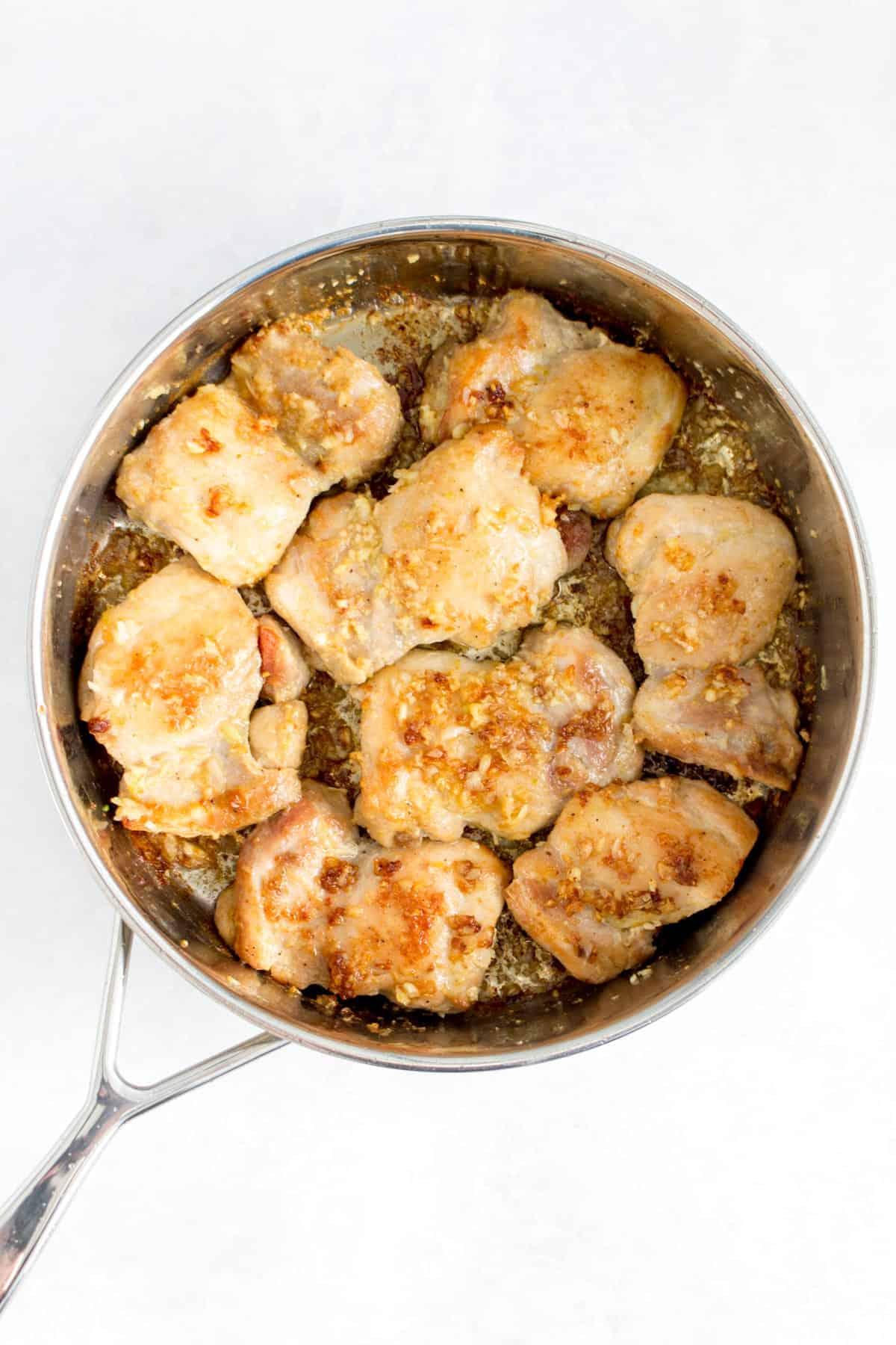 Garlic butter chicken thighs inside of a saute pan.