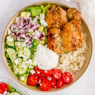 A bowl of herb chicken over top of rice and salad.