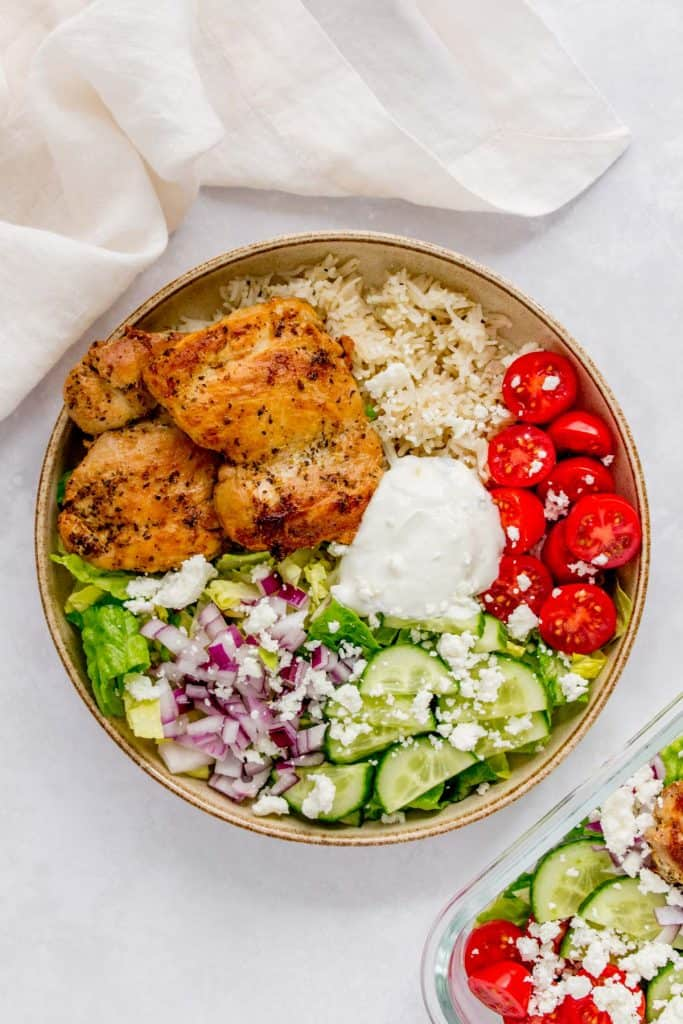 A bowl of Greek chicken over top of rice and salad.