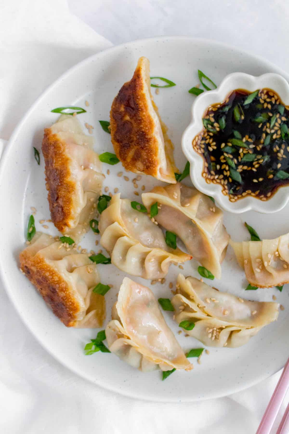 Close up of multiple pork dumplings on a plate with sesame seeds and green onion garnish.