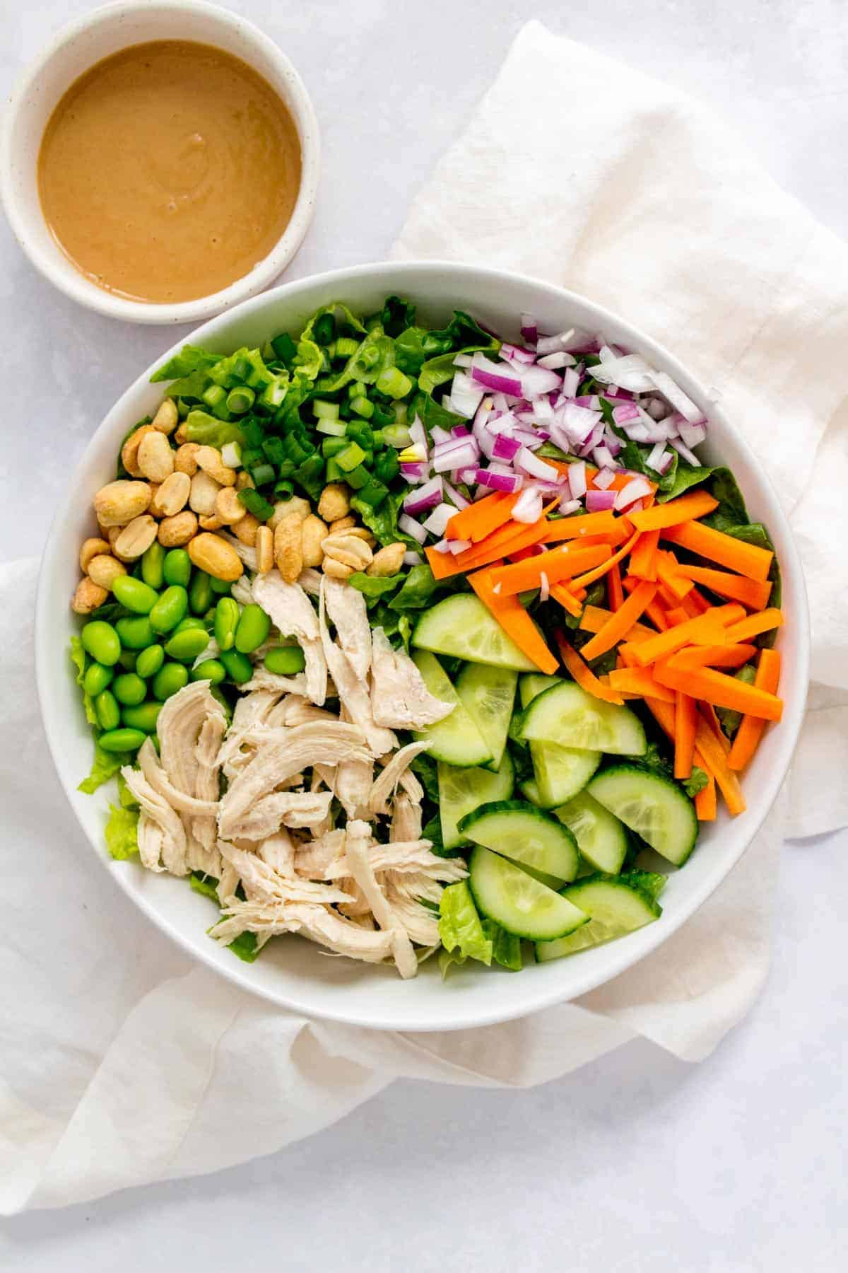 Bowl of thai chopped salad with a small bowl of peanut sauce beside it.