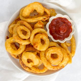 Onion rings in a plate with ketchup.