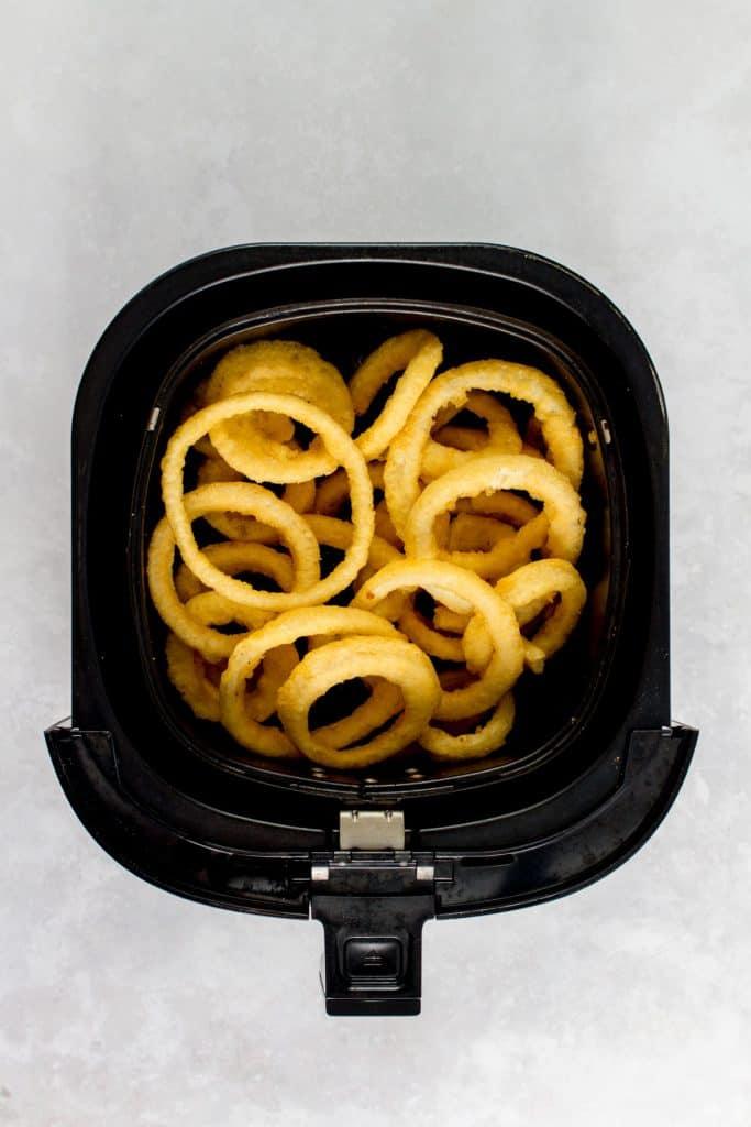 Frozen onion rings inside of a Philips XXL air fryer basket.