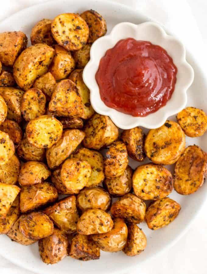 White plate of air fryer roasted potatoes with a serving of ketchup.