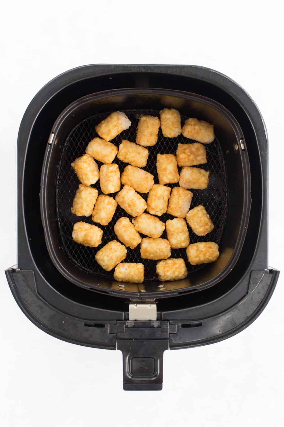 Frozen tater tots in the air fryer basket.