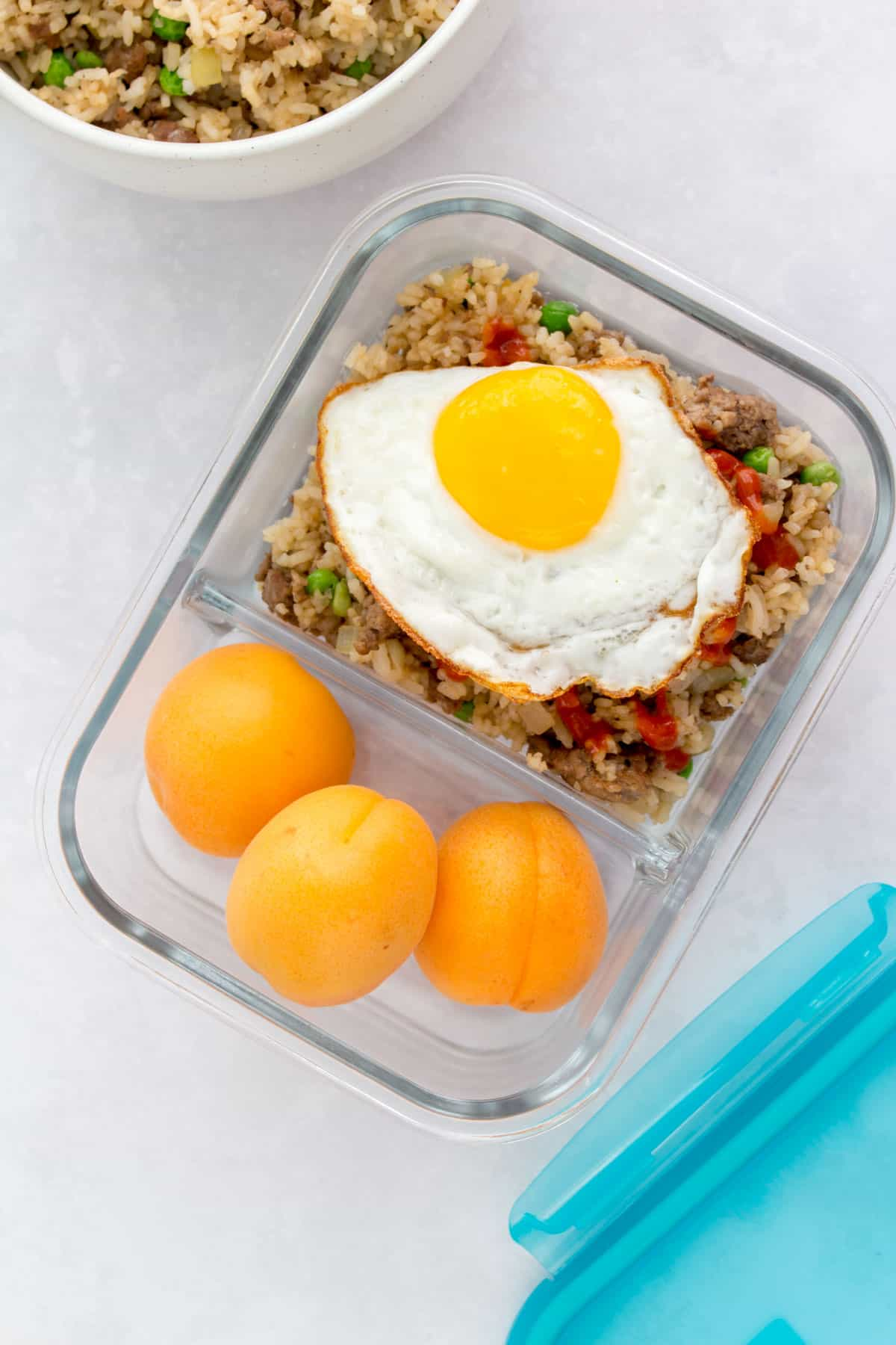 Pyrex meal prep bowl with beef fried rice and fruit.