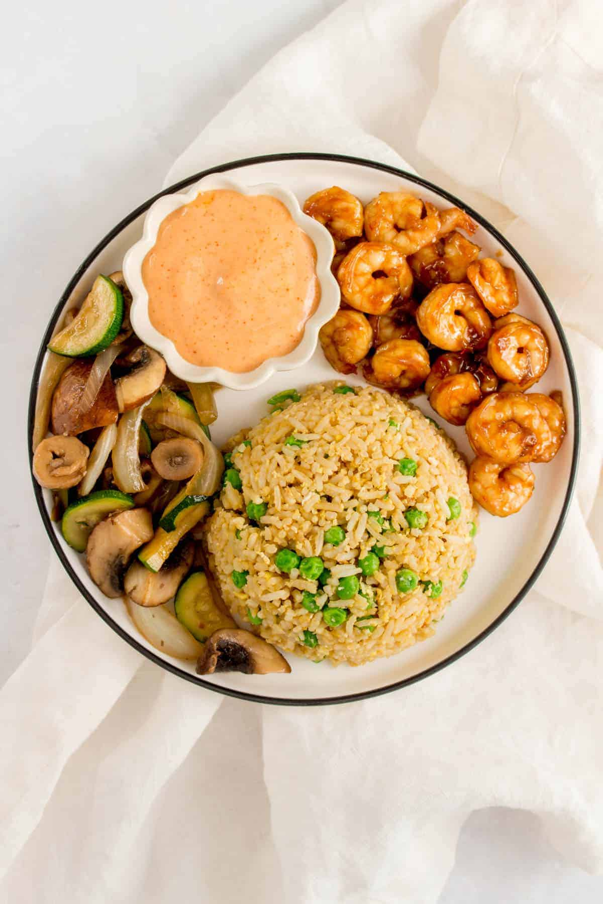 Overhead photo of a plate of hibachi shrimp, vegetables, fried rice, and yum yum sauce.