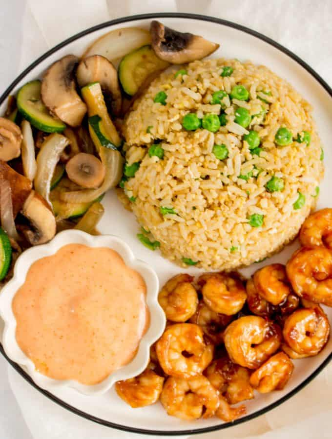 Close up of a plate of hibachi shrimp, vegetables, fried rice, and yum yum sauce.