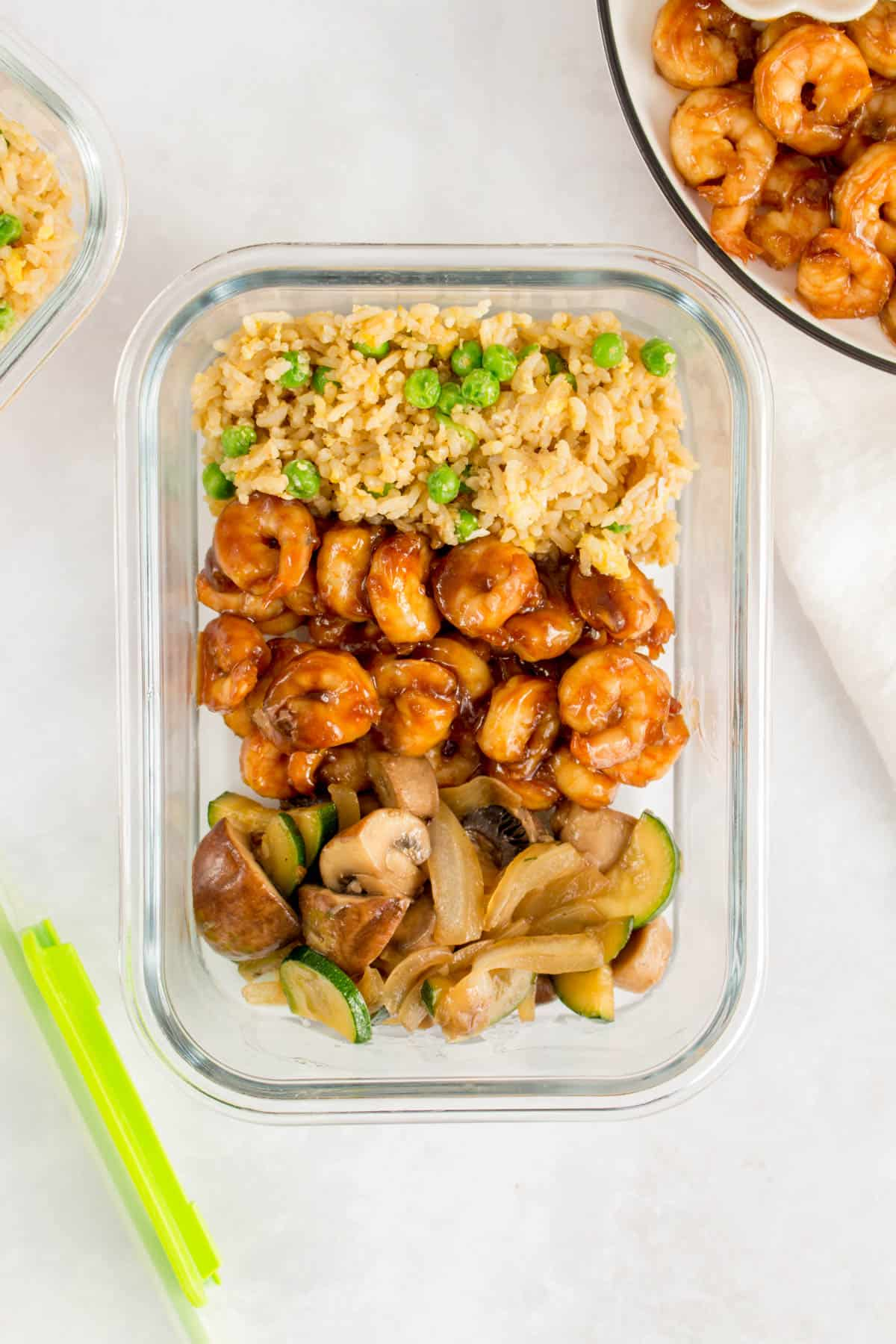Meal prep container of hibachi shrimp with fried rice and vegetables.