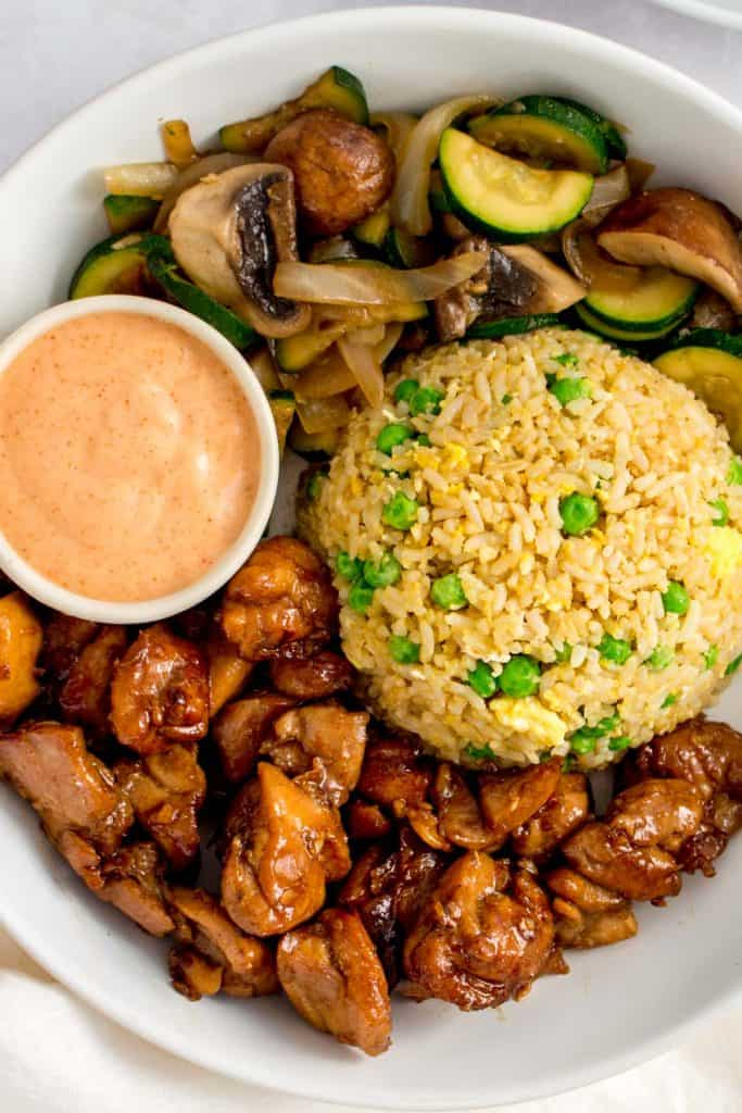 Close up of hibachi chicken on a plate with fried rice and vegetables with yum yum sauce.