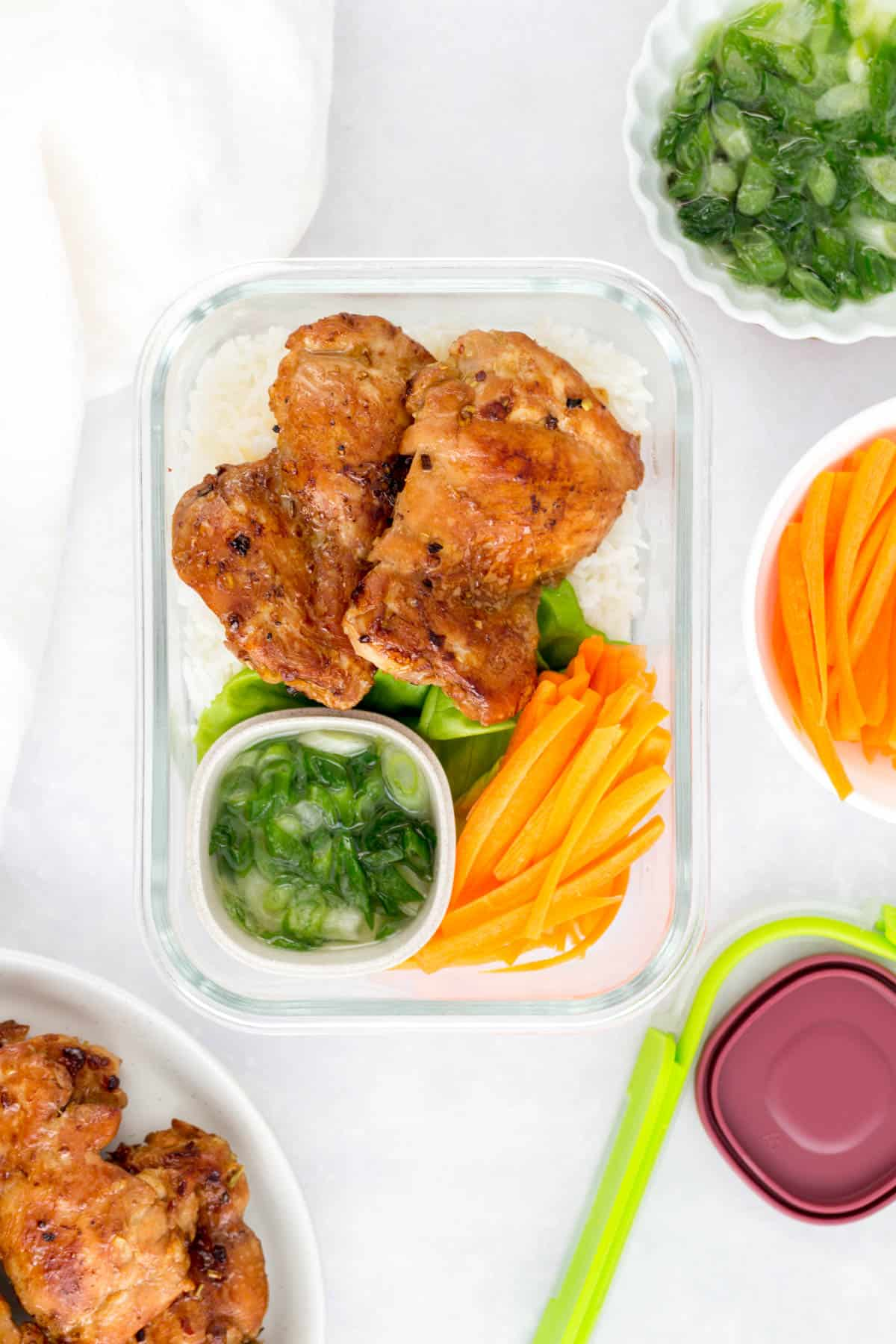 Meal prep container with rice, lemongrass chicken, lettuce, carrots, and scallion sauce.