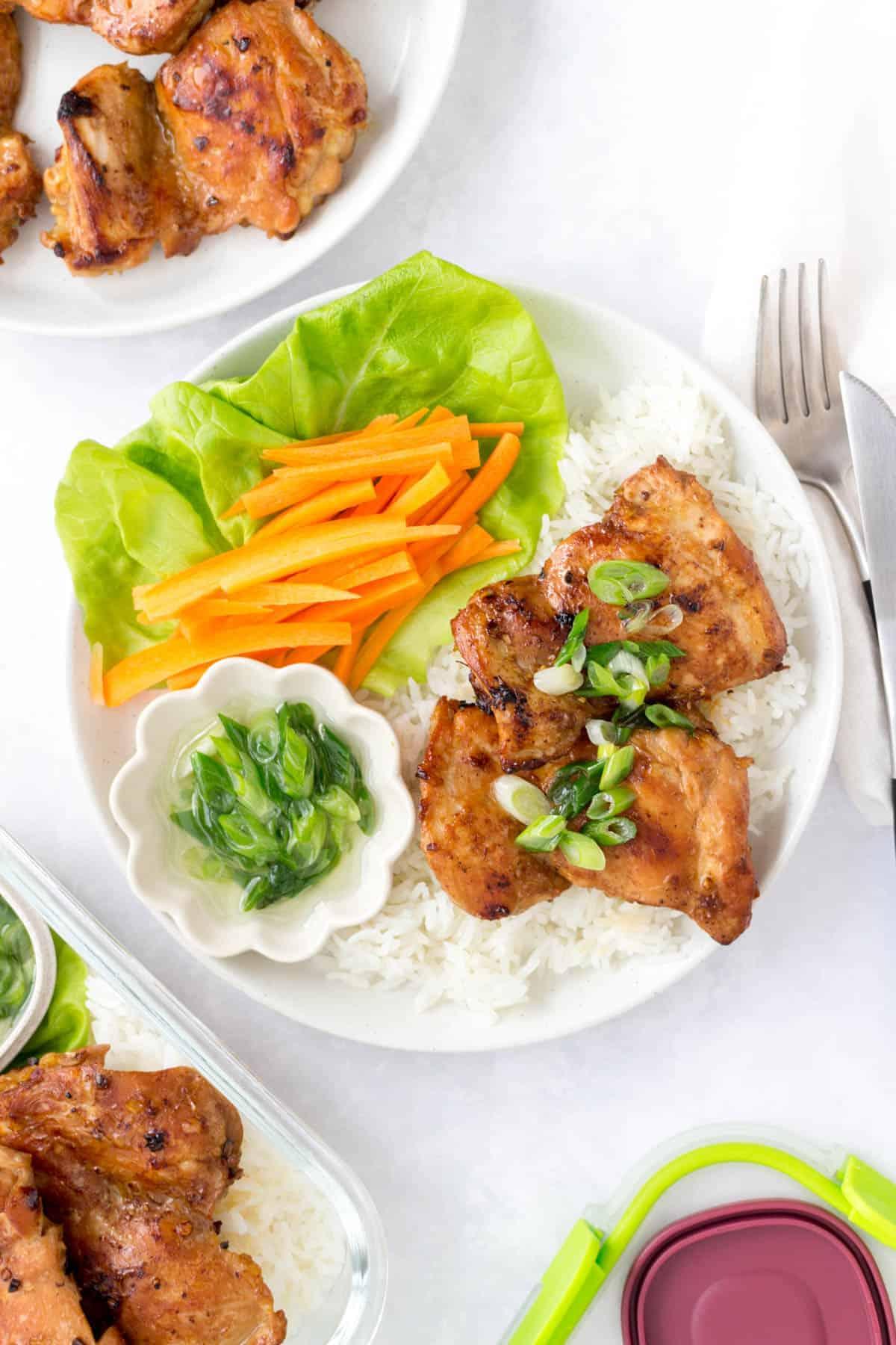 White plate with rice, lemongrass chicken, scallion oil, lettuce, and sliced carrots.