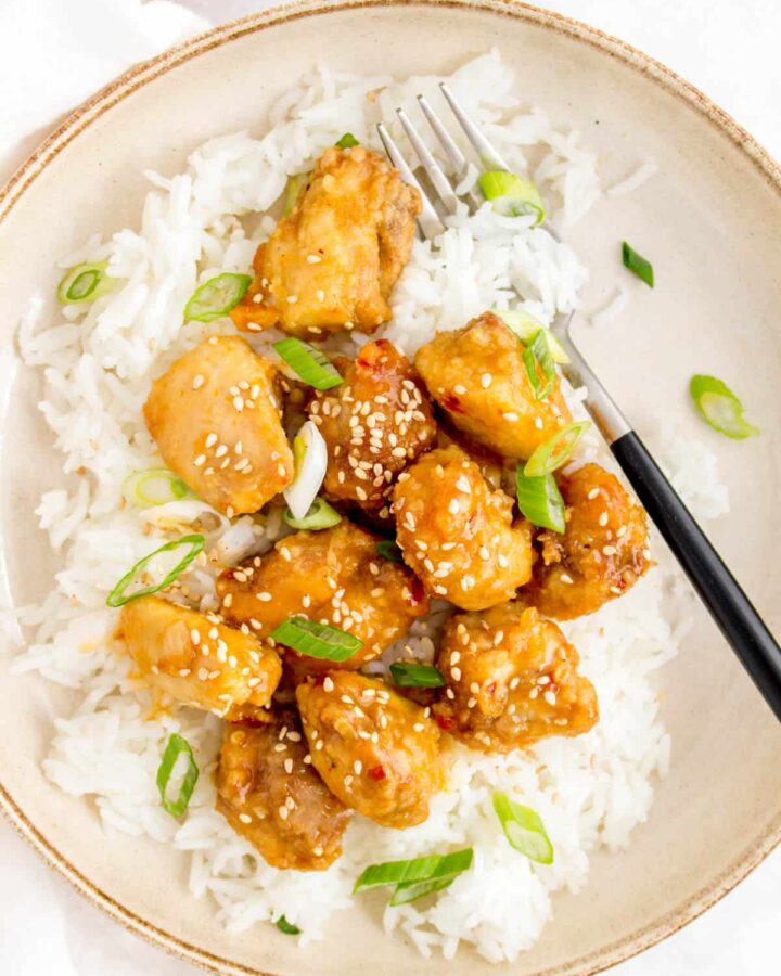 A plate of rice with air fryer orange chicken on top with a fork in the plate. Garnished with sesame seeds and green onion.