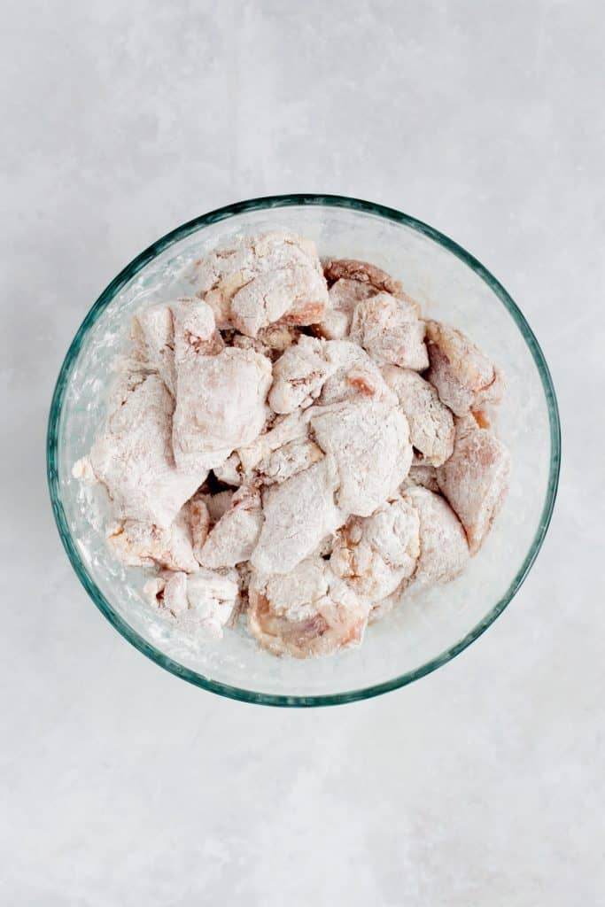 Chicken pieces covered in cornstarch in a bowl.
