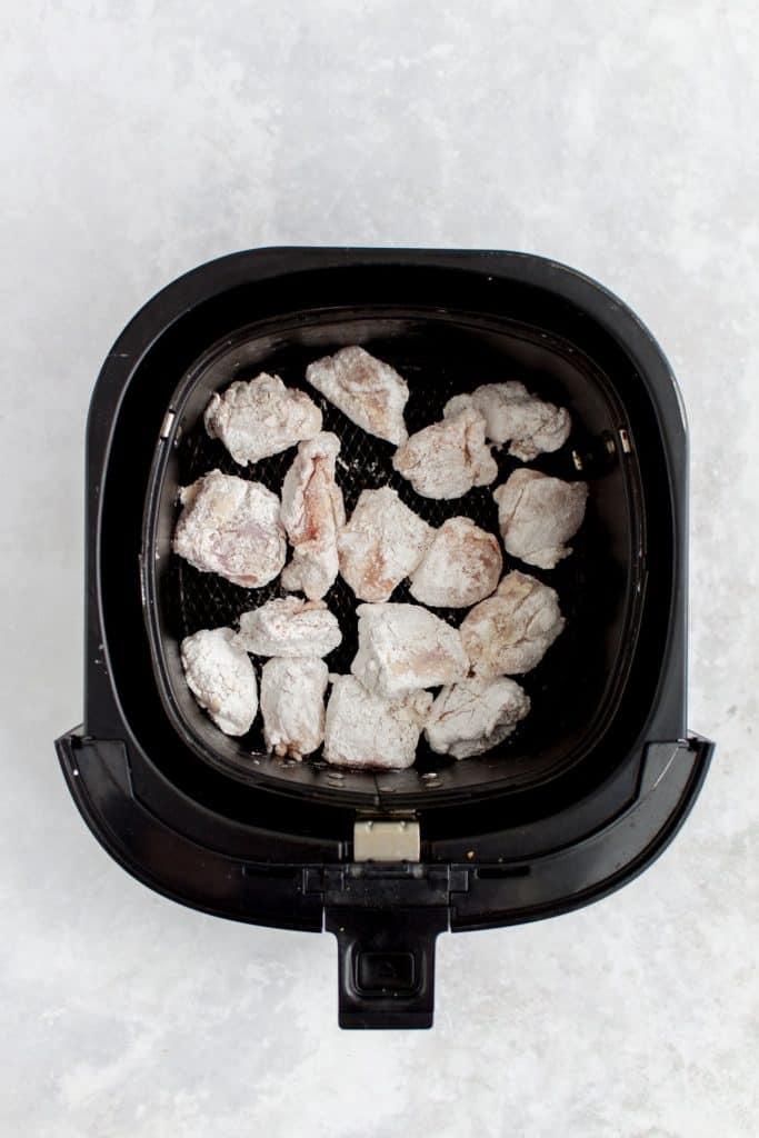 Cornstarch covered chicken pieces in an air fryer basket.