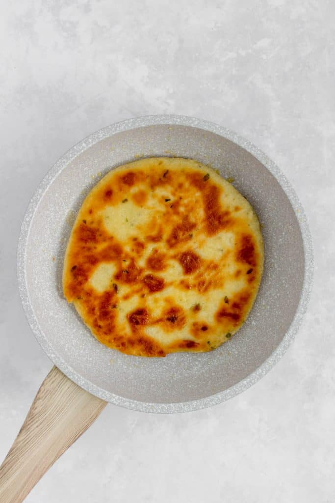 Fully cooked flatbread in a frying pan.