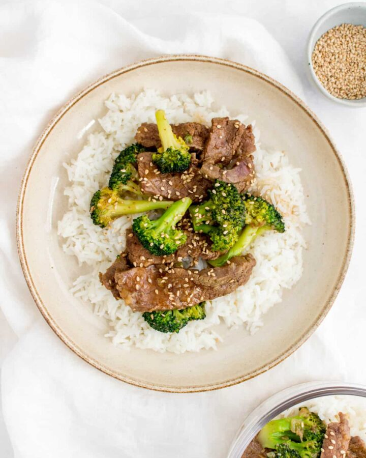 A plate of rice with beef and broccoli on top.