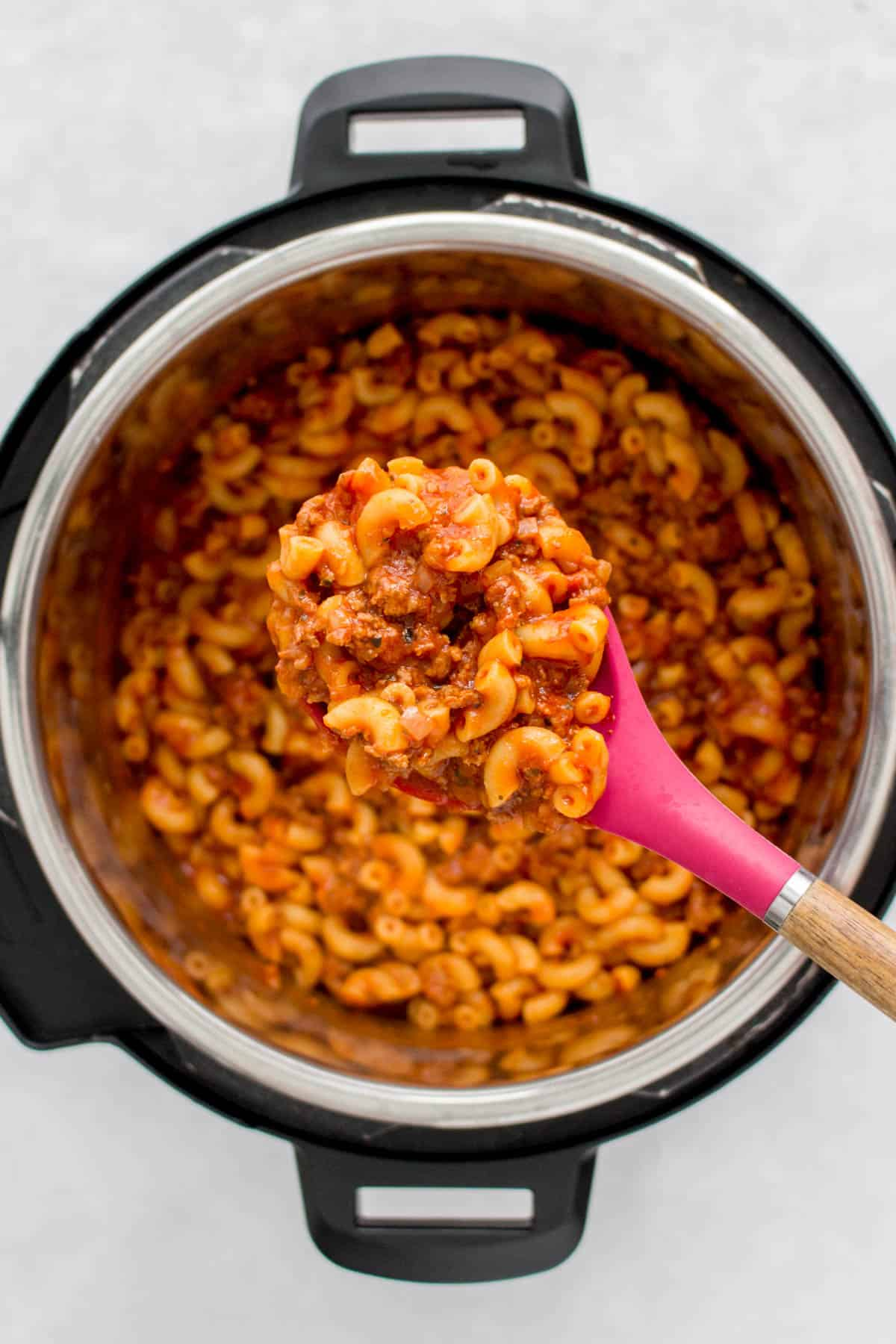 A spoonful of goulash over top of an Instant Pot.