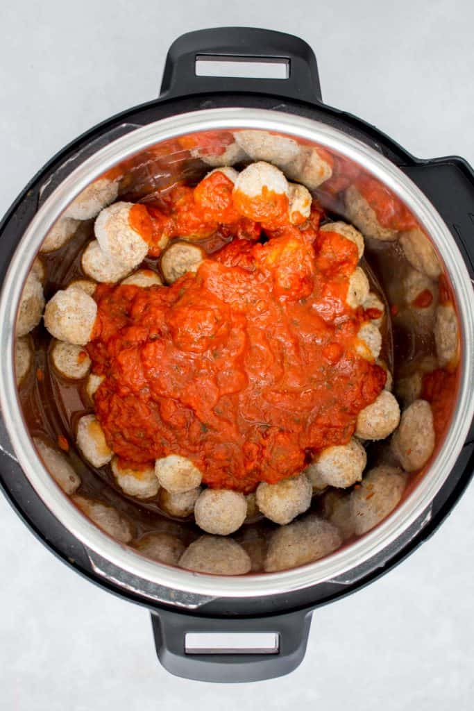 Frozen meatballs with pasta sauce over top in an Instant Pot.