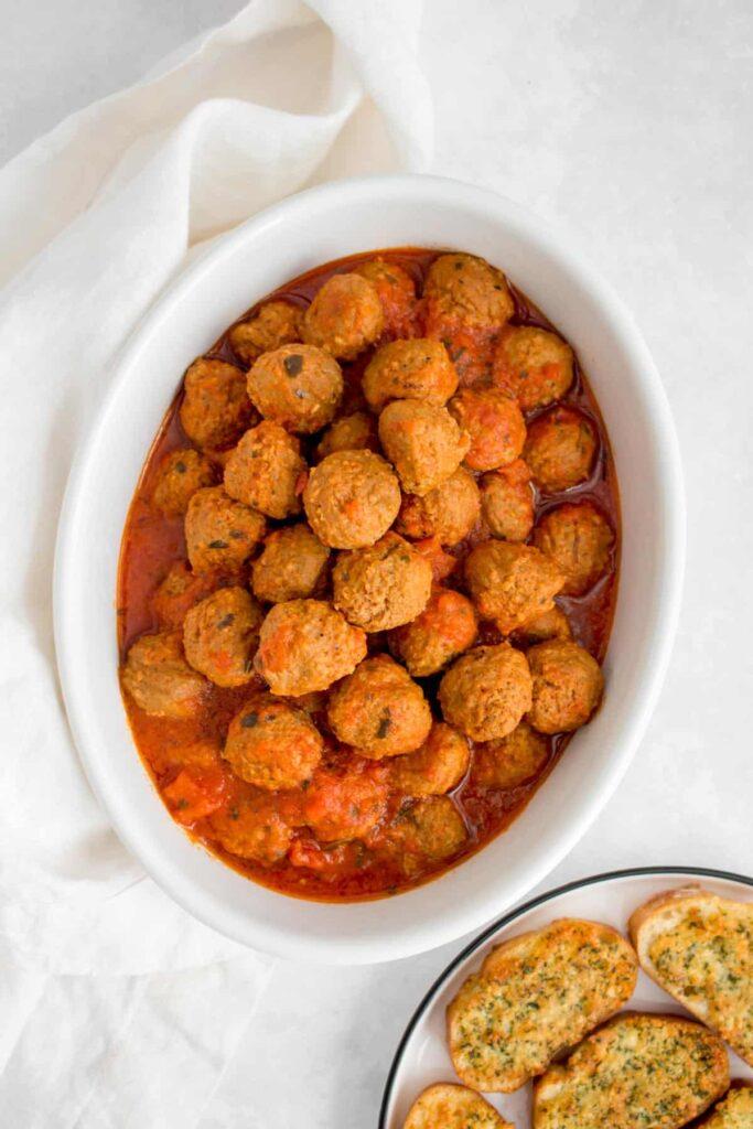 Serving platter of cooked meatballs beside garlic bread.