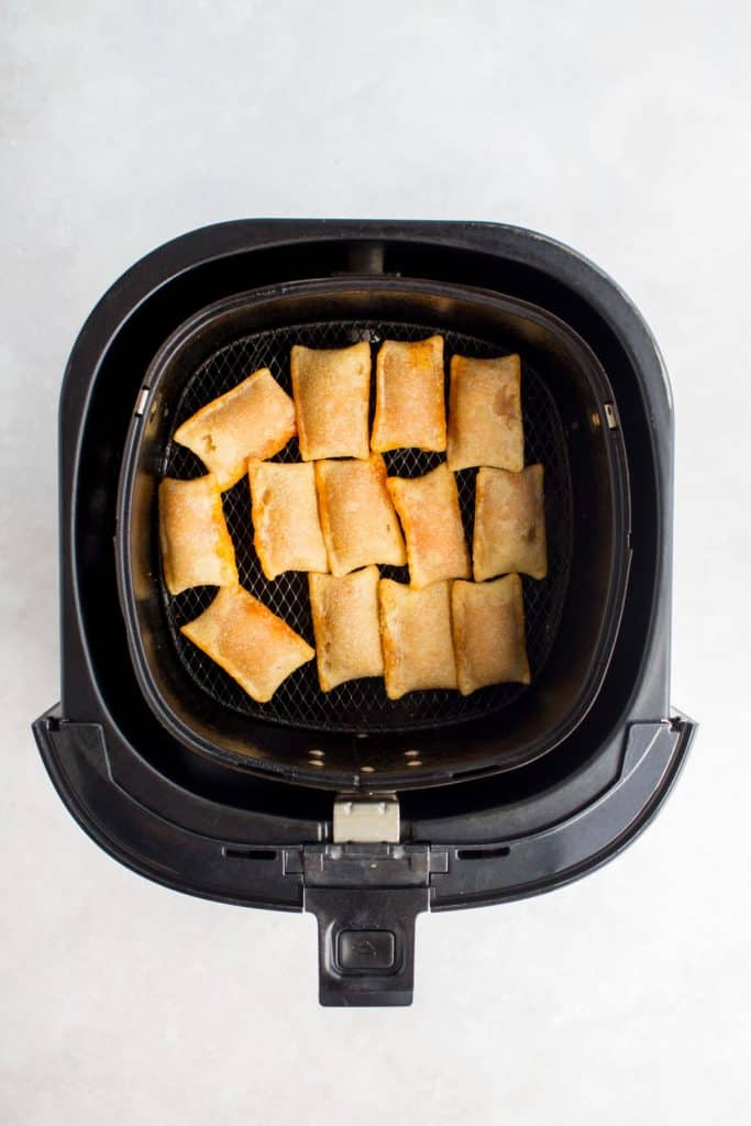 Crispy air fried pizza rolls in an air fryer basket.