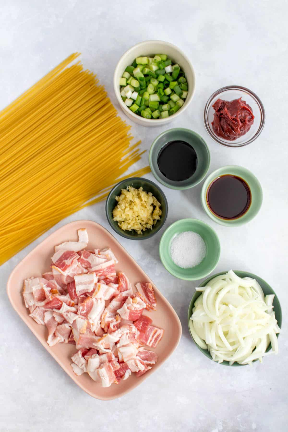 Overhead view of ingredients needed to make gochujang noodles with bacon and scallions.
