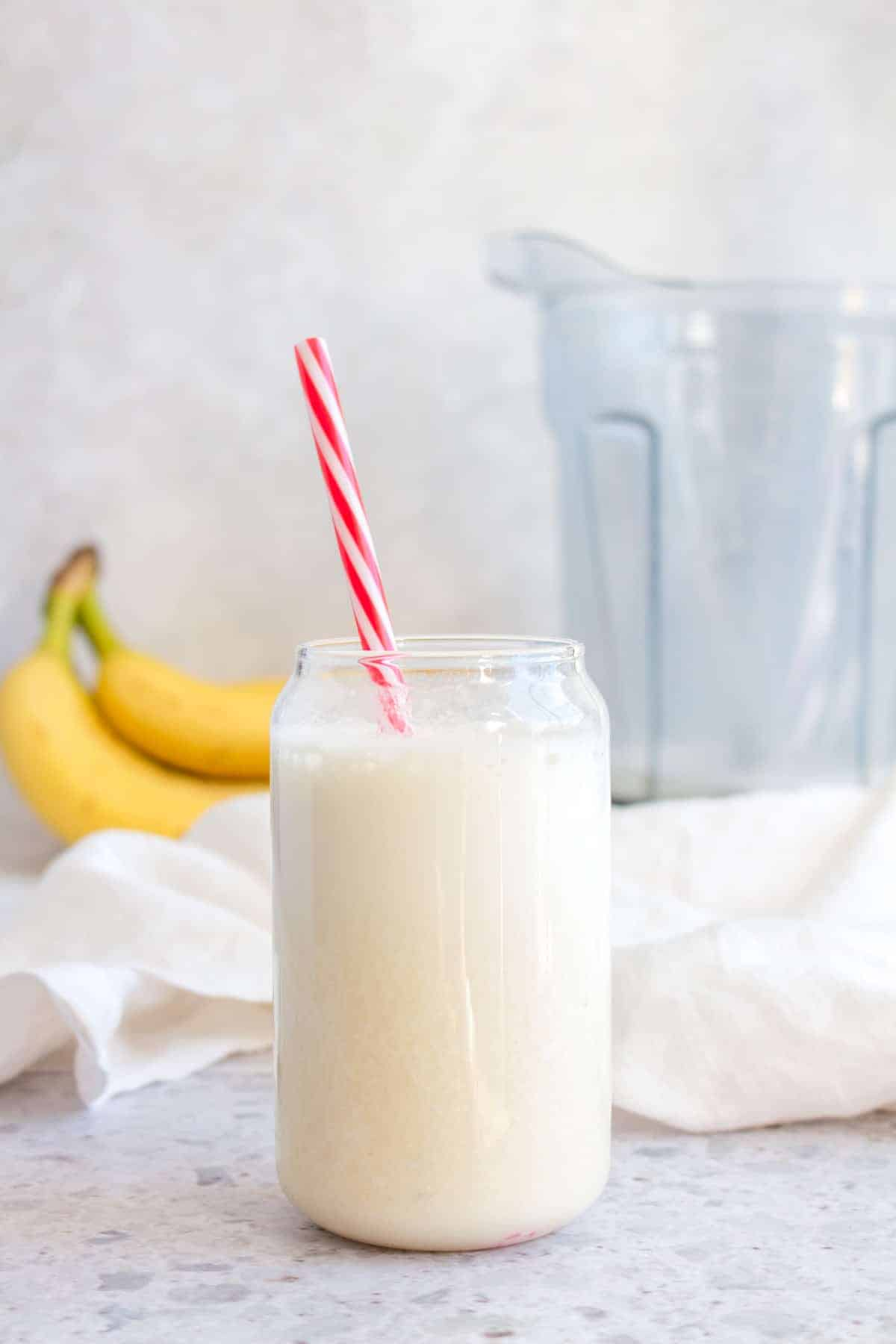 Banana milk in a cup with a red and white straw with bananas and a vitamix in the background.