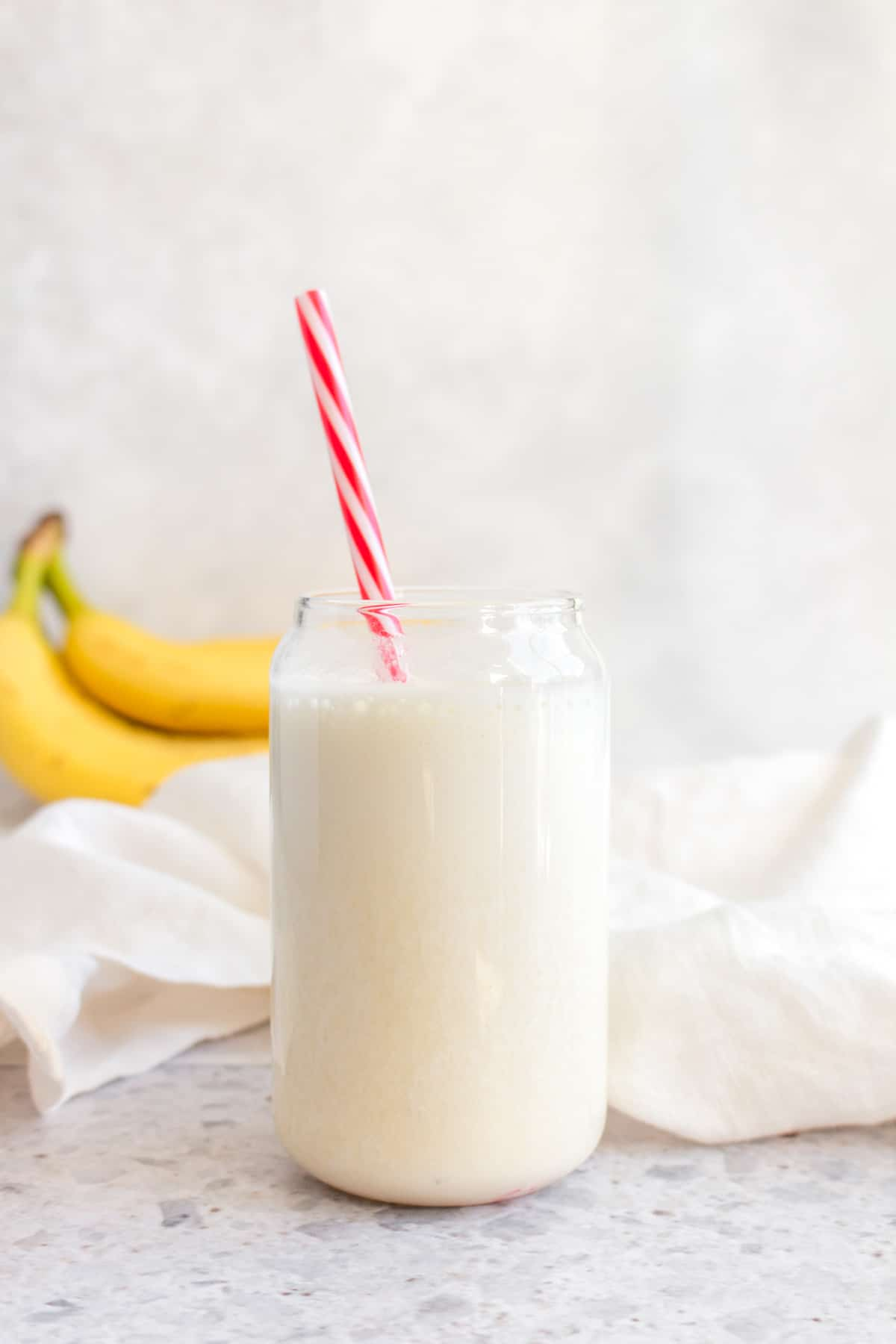 Banana milk in a cup with a red and white straw.