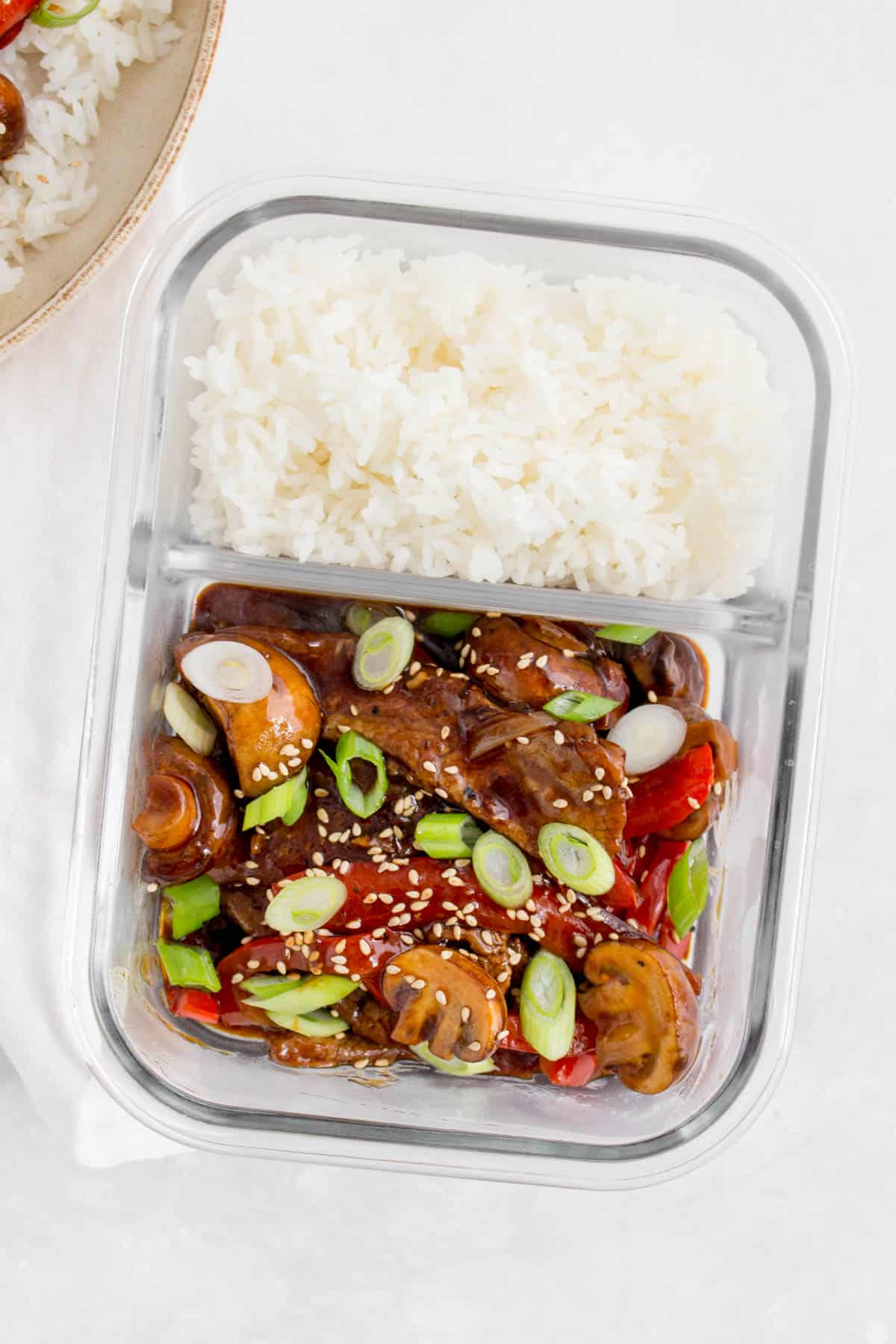 A glass meal prep container with black pepper steak in one compartment and rice in the other.