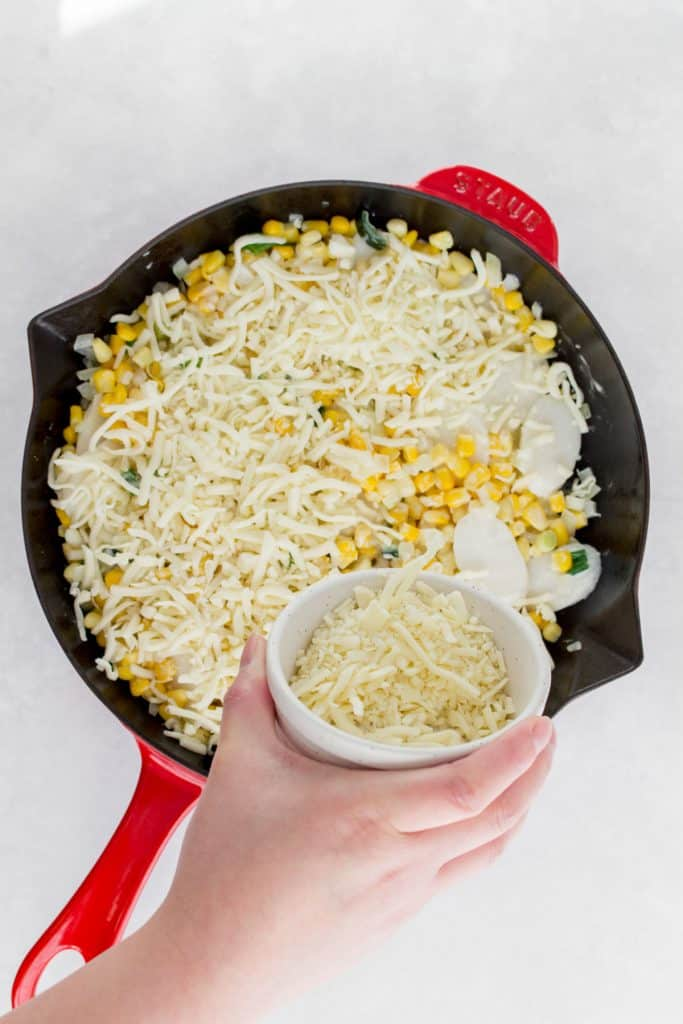 Shredded cheese added to a skillet.