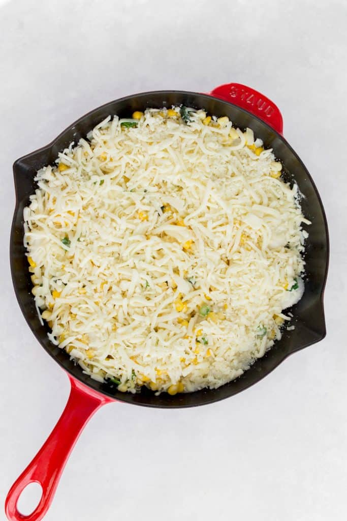 Cheese over top of corn mixture in a cast iron skillet.