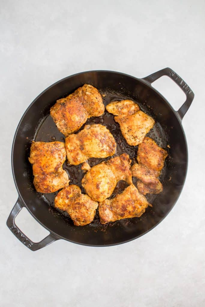 Chicken thighs searing in a pan.