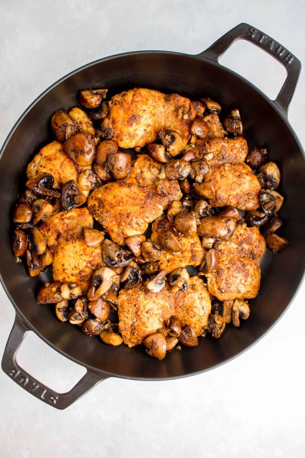 Staub braiser with chicken thighs and mushrooms.