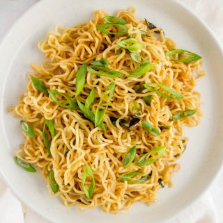 A plate of scallion noodles with sliced scallions as garnish.