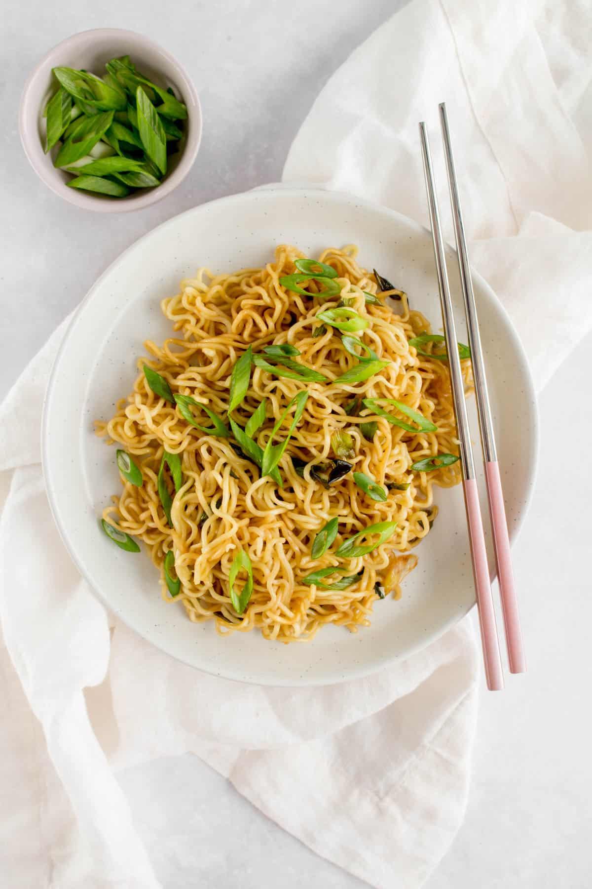 Plate of garlic scallion noodles with chopsticks beside it.